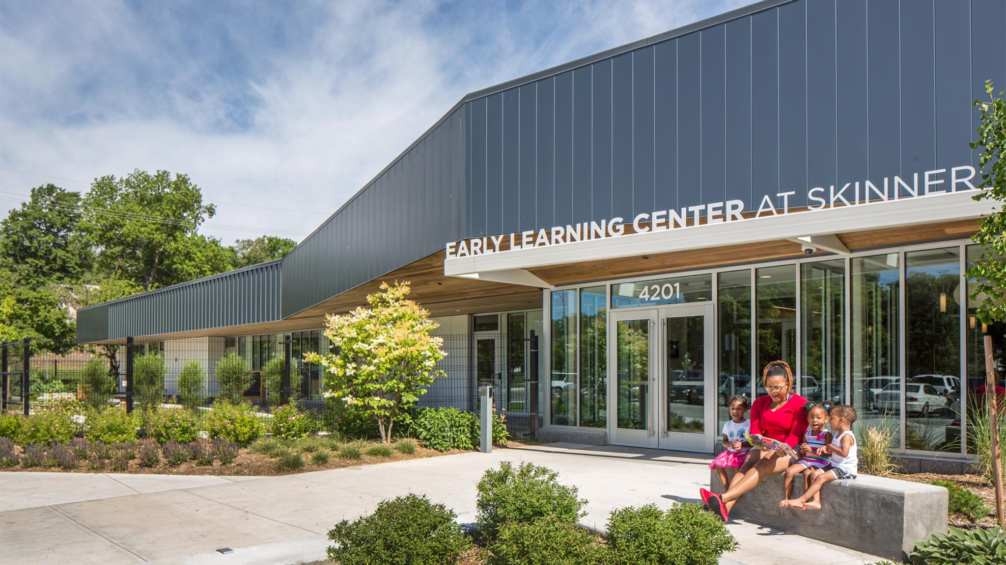 Woman with chicldren sitting outside of Skinner Early Learning Center